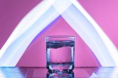 与冰的液体在反射性表面上的一块玻璃在带红色背景 免版税库存照片