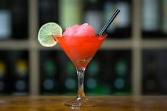 与冰的红色鸡尾酒装饰与站立在木酒吧柜台的石灰 在有瓶的背景机架上 免版税库存照片