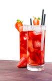 与冰的草莓鸡尾酒在草莓附近的老木桌上 免版税库存照片
