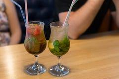 与冰的饮料在玻璃杯子在背景夏天咖啡馆的桌上站立 在一张木桌上的新鲜的冷的mojito鸡尾酒 库存照片