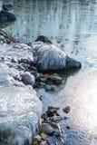 与冰的冻岩石在冬天湖 库存照片