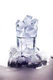 与冰的玻璃在白色背景和堆站立冰柱在底部 库存图片