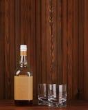 与冰的玻璃威士忌酒和瓶的在木背景 库存图片