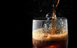 与冰飞溅的汽水玻璃在黑暗的背景 在庆祝党概念的可乐玻璃 免版税库存照片