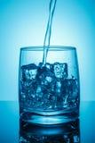 与冰,动态飞溅喷气机的一块玻璃 饮用水 倾吐水入玻璃、符号照片饮用水的,剩余和废物 免版税库存照片