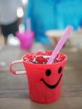 与冰水的微笑塑料红色玻璃,当室外餐馆时 免版税库存照片
