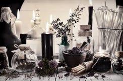 与冶金瓶子和瓶的被定调子的静物画和在桌上的神秘的对象 图库摄影