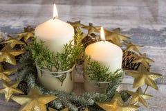 与冷杉分支和杉木锥体的灼烧的蜡烛与金黄花圈 免版税图库摄影