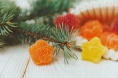 与冷杉分支和枣糖果的圣诞节构成在被编织的白色帽子 橙色甜花 库存图片