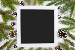 与冷杉分支和锥体的圣诞节框架 时髦大模型拷贝空间 在白色木的平的位置新年好平的位置 免版税库存照片