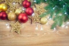 与冷杉分支的圣诞装饰在木背景、球和星、金子和红色,拷贝空间 图库摄影