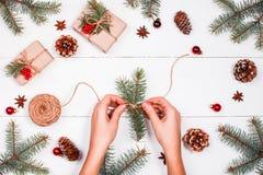与冷杉的圣诞节背景分支,杉木锥体,黄麻,红色装饰丝球  女性现有量 Xmas和新年快乐composit 免版税库存照片