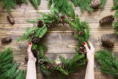 与冷杉的圣诞节花圈在木板在女性手上分支 顶视图 库存图片