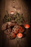 与冷杉的巧克力曲奇饼在与蜡烛1的木背景分支 免版税库存照片