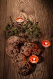 与冷杉的巧克力曲奇饼在与蜡烛1的木背景分支 库存图片