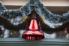 与冷杉针的圣诞节红色大塑料传统响铃 库存照片