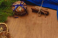 与冷杉,围巾,干桔子,锥体,饼干,桂香的圣诞节背景 免版税库存照片