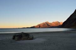 与冷的蓝色波浪的长的白色结冰的在山的海滩和阳光在远的距离 免版税图库摄影