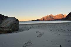 与冷的蓝色波浪的长的白色结冰的在山的海滩和阳光 免版税库存图片