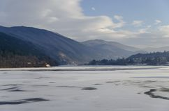 与冻湖、多雪的山、沼地、森林和保加利亚村庄Pancharevo,索非亚住宅区的场面  免版税库存图片
