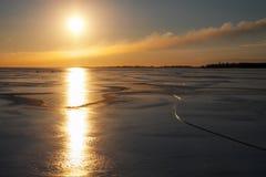 与冻湖和日落火热的天空的冬天风景 免版税库存图片