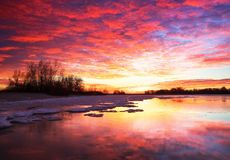 与冻湖和日落的美好的五颜六色的冬天风景 免版税库存照片