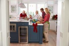 与准备圣诞节膳食的祖父母的家庭在厨房里 免版税图库摄影