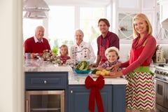 与准备圣诞节膳食的祖父母的家庭在厨房里 库存图片