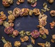 与凋枯的,干玫瑰的框架与正文,在木土气背景顶视图的葡萄酒样式 免版税库存照片
