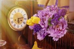 与减速火箭的时钟花的春天照片在篮子箱子 免版税库存图片