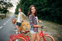 与减速火箭的自行车的年轻人和妇女姿势 图库摄影
