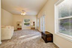 与出口的晴朗的宽敞客厅内部对后院 库存照片