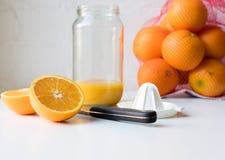 与刀子和玻璃瓶子的橙色一半 库存照片