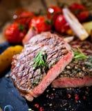与刀子的切的烤肉烤肉雕刻在黑石板岩的牛排Striploin和叉子集合 图库摄影