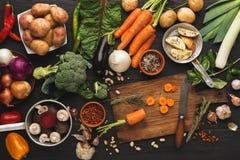 与刀子的切的红萝卜在木切板,背景 免版税库存图片