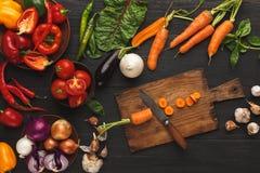 与刀子的切的红萝卜在木切板,背景 免版税图库摄影