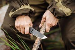 与刀子的少妇猎人切开了一根木棍子 库存照片