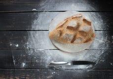 与刀子的新鲜的被烘烤的面包在土气厨房用桌上 图库摄影