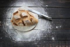 与刀子的新鲜面包在土气厨房用桌上 库存图片