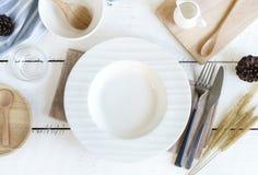 与刀子的空的在老木背景的盘和叉子 免版税库存图片