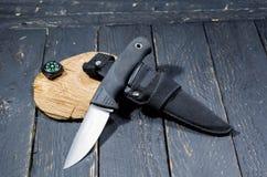 与刀鞘和指南针的刀子猎人在黑木背景 库存图片