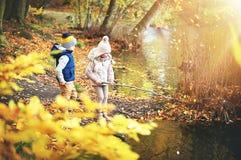 与分支的两个孩子在池塘附近 免版税图库摄影