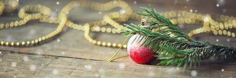 与分支的长的横幅云杉,红色圣诞节球和成串珠状在木背景 invitation new year 库存照片
