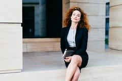 与分蘖性波浪发、红色嘴唇和光亮的眼睛的可爱的女性模型,正式地穿戴,当盘她的腿,拿着片剂wi时 免版税库存照片