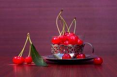 与切口的成熟红色樱桃在有铁边缘的一个杯子 库存图片