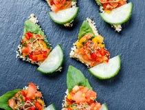 与切好的菜和芝麻的开胃菜点心在石板岩背景关闭 免版税库存图片
