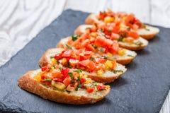 与切好的菜的开胃菜bruschetta在石板岩背景关闭的ciabatta面包 库存图片