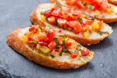 与切好的菜的开胃菜bruschetta在石板岩背景关闭的ciabatta面包 图库摄影