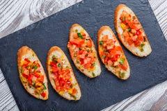 与切好的菜的开胃菜bruschetta在石板岩背景关闭的ciabatta面包 免版税图库摄影