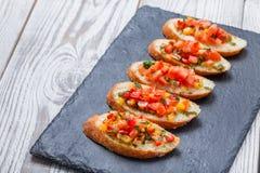 与切好的菜的开胃菜bruschetta在石板岩背景关闭的ciabatta面包 库存照片